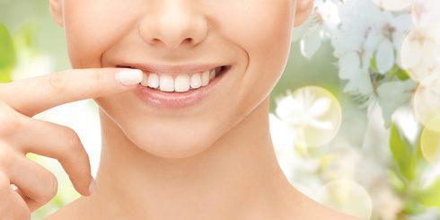 Frau zeigt auf weiße Zähne in ihrem Mund durch Kurkuma - Zahnpasta